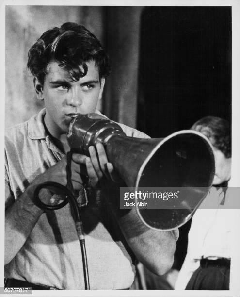 Actor Fabian Forte talking into a loud hailer on a film set circa 1960