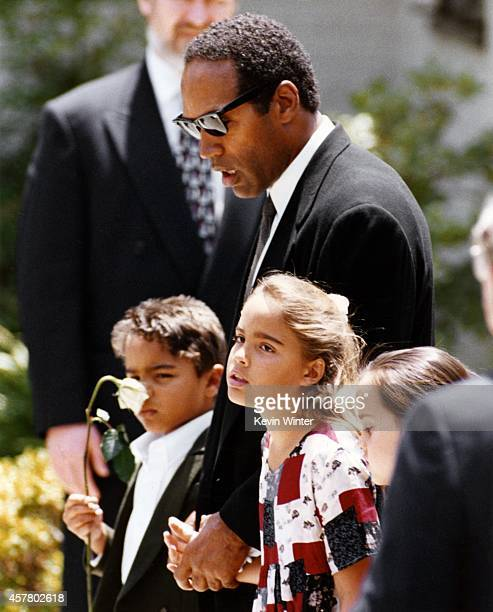 Actor football star and soon to be accused murderer OJ Simpson with his children Justin Simpson and Sydney Simpson at the funeral of their slain...