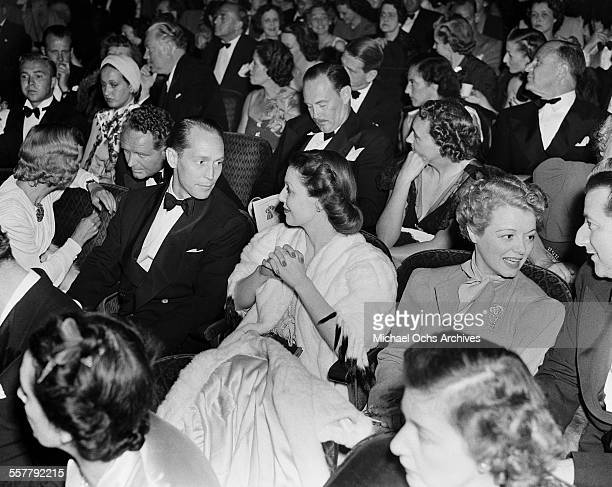Actor Franchot Tone talks with actress Loretta Young seated next to Janet Gaynor during an event in Los Angeles California