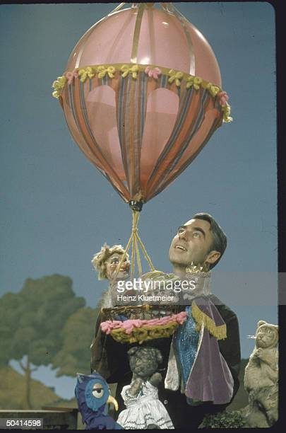 Actor Fred Rogers holding a balloon and puppets in the public TV childrens program Mister Rogers' Neighborhood