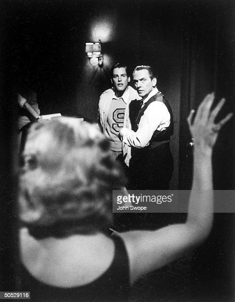 Actor Fredric March playing Willie Loman in the movie Death of a Salesman is discovered with another woman by actor Kevin McCarthy playing his son...