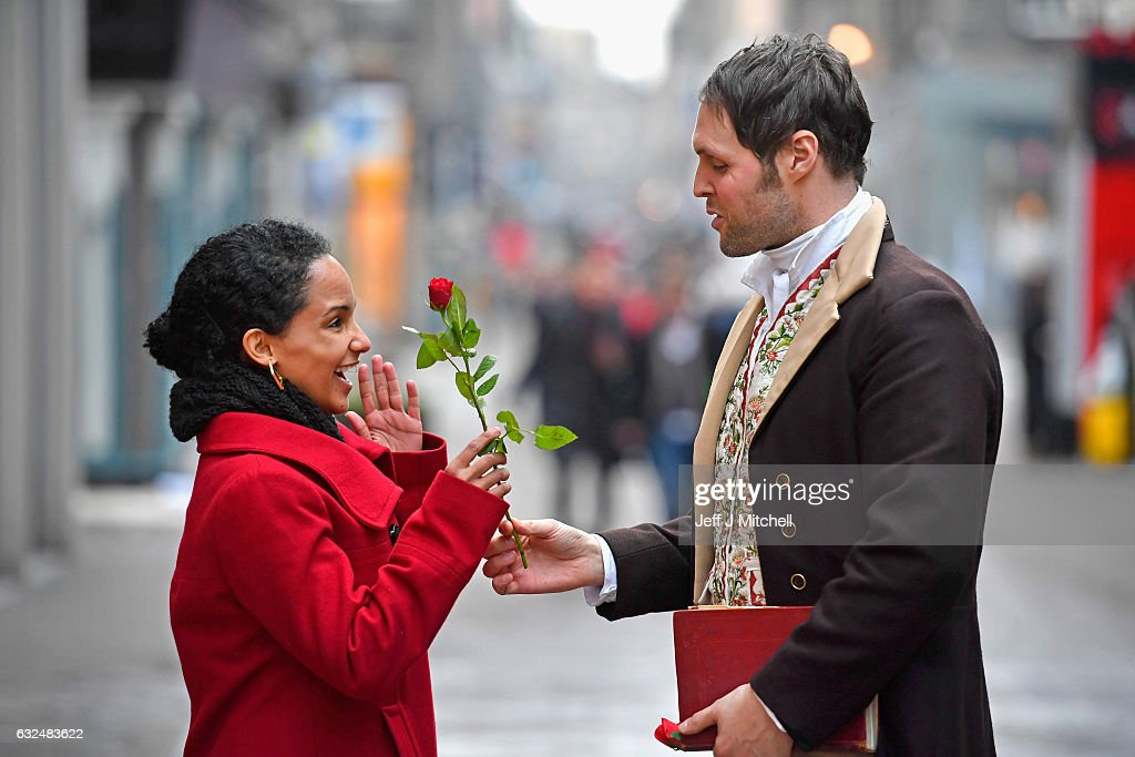Red red rose street festival takes place over burns night photos and actor gareth morrison dressed as robert burns hands a red rose to a tourist to promote m4hsunfo