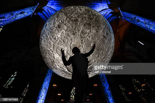 Actor Gareth Morrison, poses as poet Robert Burns in front of artwork by artist Luke Jerram in St Giles Cathedral on January 21, 2019 in Edinburgh,...