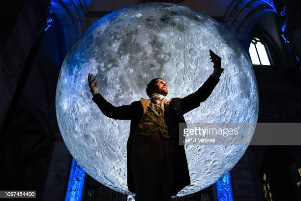 Actor Gareth Morrison poses as poet Robert Burns in front of artwork by artist Luke Jerram in St Giles Cathedral on January 21 2019 in Edinburgh...