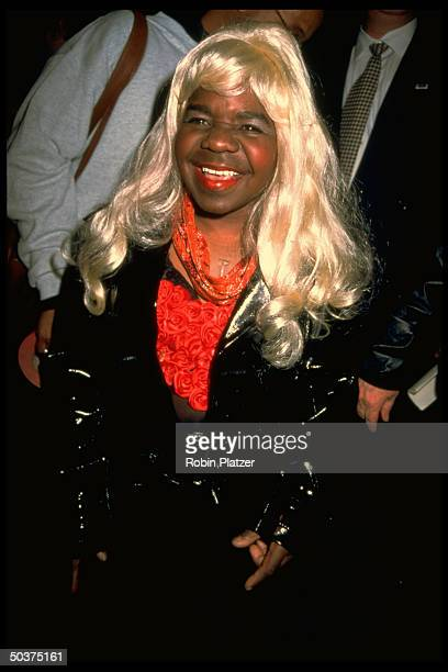 Actor Gary Coleman wearing a platinum wig and a snappy black raincoat at a Victoria's Secret fashion show