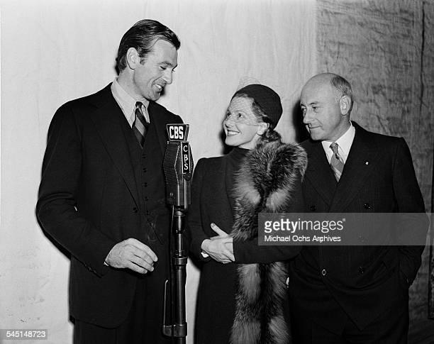 Actor Gary Cooper actress Jean Arthur and director Cecil B Demille speak at the premire of The Plainsman in Los Angeles California