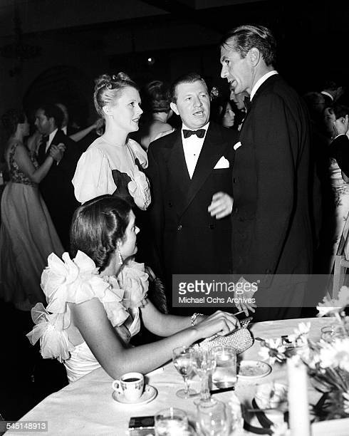 Actor Gary Cooper and wife Veronica Balfe chat with actress Mary Astor at an event in Los Angeles California
