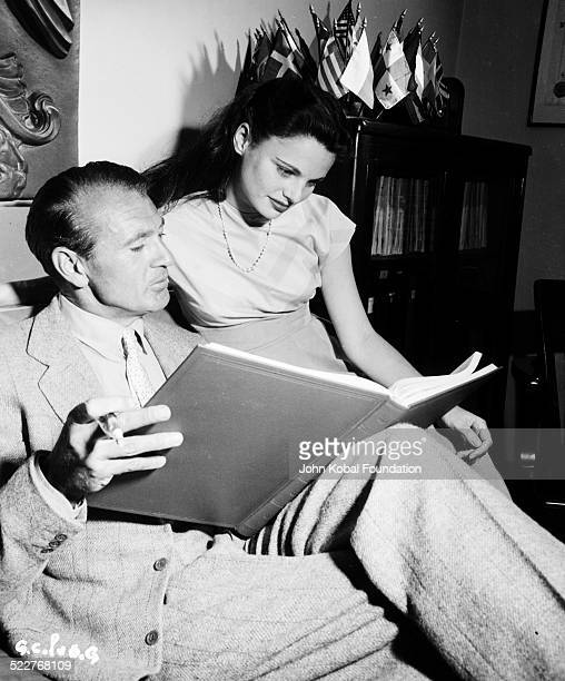 Actor Gary Cooper reading a large book as a woman looks over his shoulder 1950
