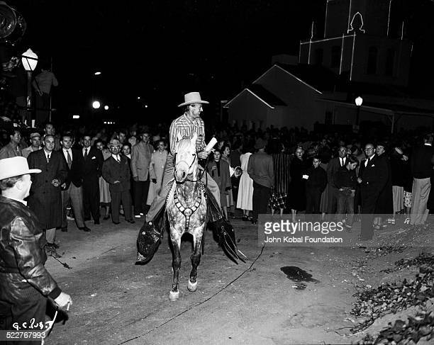 Actor Gary Cooper riding a horse in front of a crowd of onlookers circa 1940