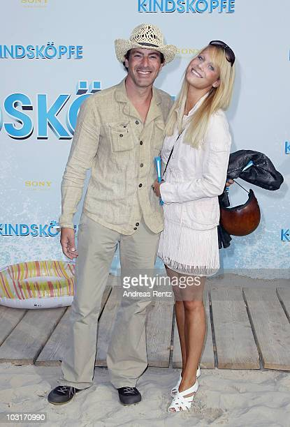 Actor Gedeon Burkhard and Annika Bohrmann attend the Beach BBQ for the German Premiere of 'Kindskoepfe' at O2 World on July 30 2010 in Berlin Germany