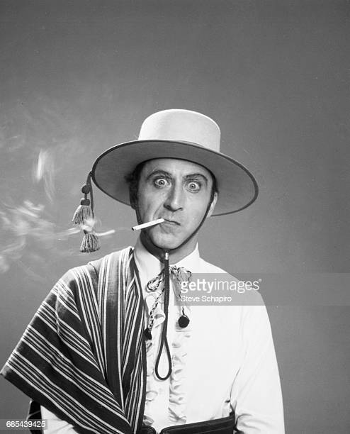 Actor Gene Wilder dressed in costume as the silent screen star Rudolph Valentino, 1977. He is smoking a cigarette and wearing a hat, mimicking...