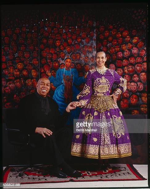 Actor Geoffrey Holder with his wife Carmen De Lavallade, wearing an outfit of his design, and standing in front of a painting by Holder are...
