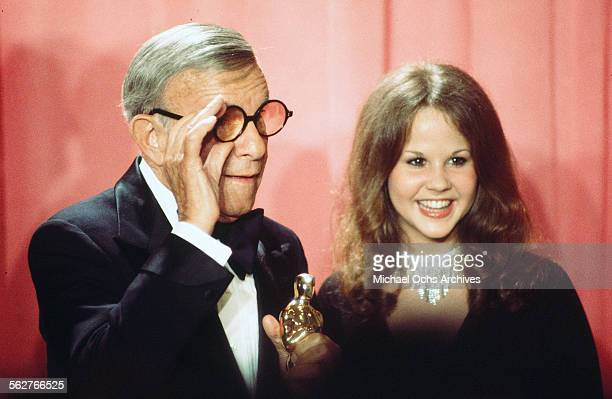 Actor George Burns with actress Linda Blair poses backstage after winning Best Supporting Actor award during the 48th Academy Awards at Dorothy...
