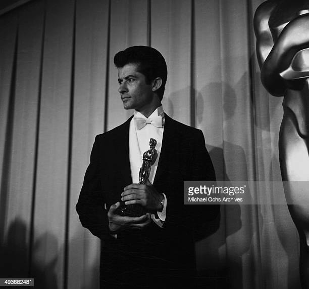 "Actor George Chakiris poses with his Academy Award for Actor in a Supporting Role in ""West Side Story"" in Los Angeles, California."