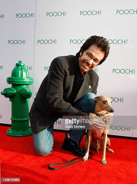 Actor George Chakiris poses with his dog Max at the grand opening of the fourth Pooch Hotel on May 3 2012 in Hollywood California The Pooch Hotel is...