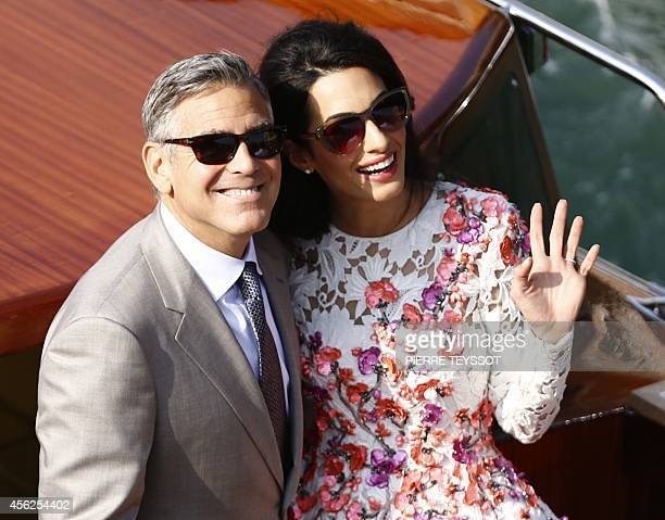 US actor George Clooney and his wife Amal Alamuddin stand on a taxi boat on the Grand Canal on September 28 2014 in Venice Hollywood heartthrob...