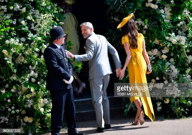 US actor George Clooney and his wife Amal Clooney arrive for the wedding ceremony of Britain's Prince Harry Duke of Sussex and US actress Meghan...