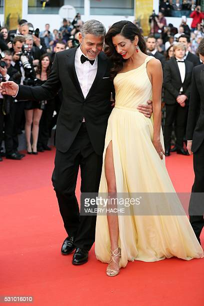 TOPSHOT US actor George Clooney and his wife Amal Clooney arrive on May 12 2016 for the screening of the film Money Monster at the 69th Cannes Film...