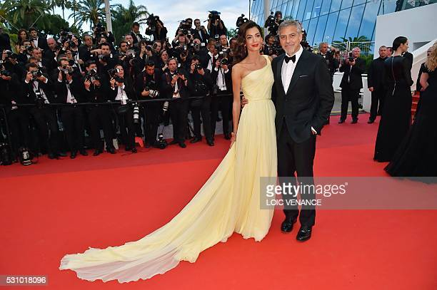 US actor George Clooney and his wife BritishLebanese lawyer Amal Clooney pose on May 12 2016 as they arrive for the screening of the film Money...