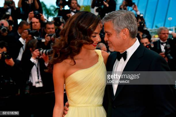 TOPSHOT US actor George Clooney and his wife BritishLebanese lawyer Amal Clooney pose on May 12 2016 as they arrive for the screening of the film...