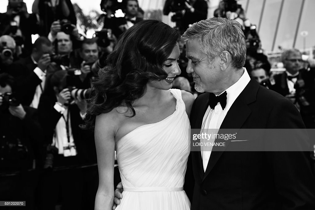 US actor George Clooney (R), and his wife British-Lebanese lawyer Amal Clooney pose on May 12, 2016 as they arrive for the screening of the film 'Money Monster' at the 69th Cannes Film Festival in Cannes, southern France. / AFP / LOIC