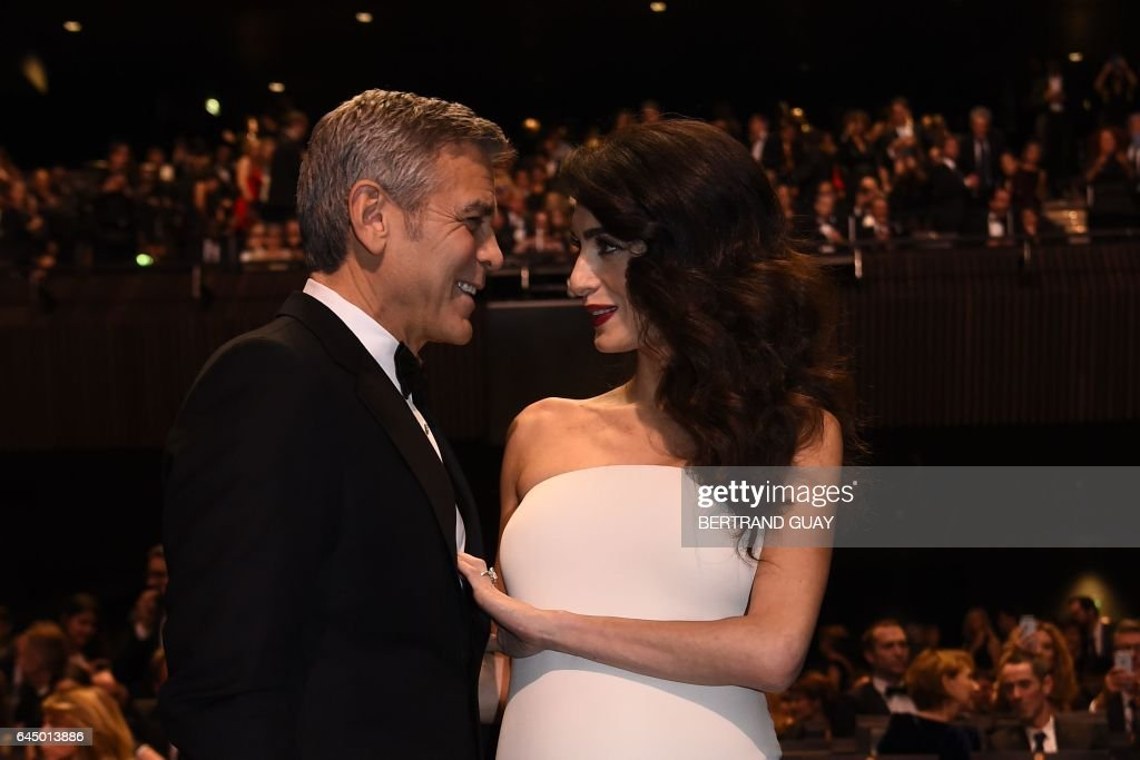 TOPSHOT - US actor George Clooney (L) and his wife British-Lebanese lawyer Amal Clooney pose as they arrive for the 42nd edition of the Cesar Ceremony at the Salle Pleyel in Paris on February 24, 2017. / AFP / bertrand GUAY