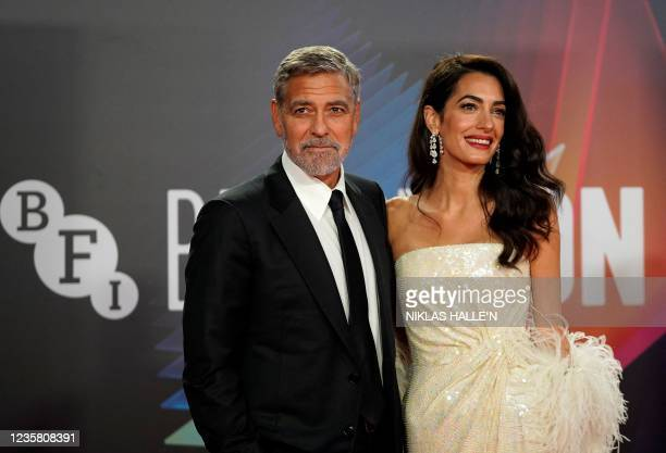 Actor George Clooney and his wife Lebanese-British barrister Amal Clooney pose on the red carpet on arrival to attend the UK premiere of the film...
