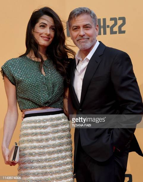 "Actor George Clooney and wife British-Lebanese Amal Clooney pose for photographs as they arrive to the premiere of ""Catch-22"" on May 13, 2019 in Rome"