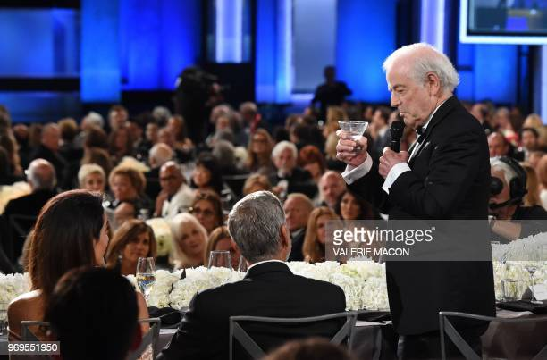US actor George Clooney flanked by his wife BritishLebanese barrister Amal Clooney listens as his father Nick Clooney delivers a toast at the 46th...