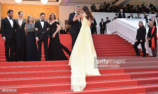 US actor George Clooney holds on May 12 2016 the hand of his wife BritishLebanese lawyer Amal Clooney as she joins British actor Dominic West Irish...