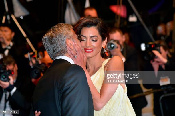 TOPSHOT US actor George Clooney kisses his wife BritishLebanese lawyer Amal Clooney as they leave on May 12 2016 the Festival Palace after the...