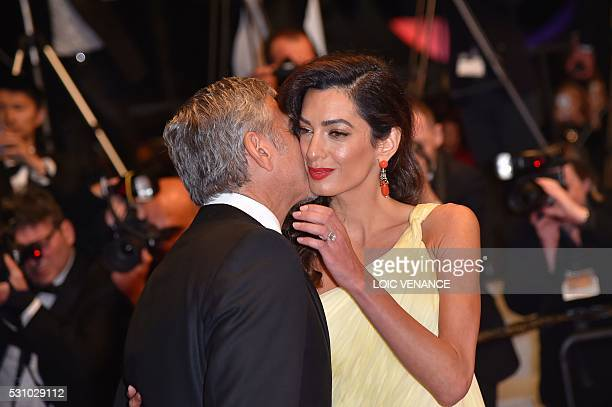US actor George Clooney kisses his wife BritishLebanese lawyer Amal Clooney as they leave on May 12 2016 the Festival Palace after the screening of...