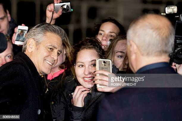 US actor George Clooney poses for pictures with fans as he arrives at the Goed Geld Gala charity event at the Carre Theatre in Amsterdam on January...