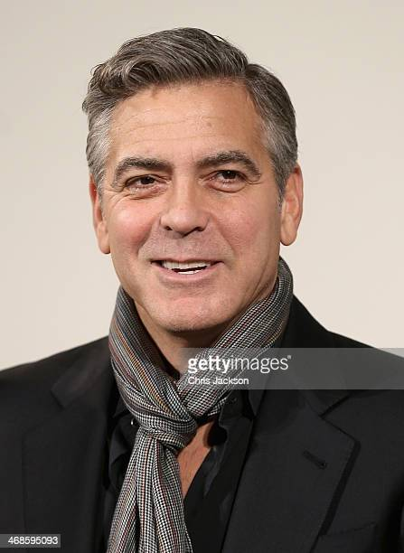 """Actor George Clooney poses in fron of the painting 'Cupid Complaining to Venus' by Lucas Cranach the Elder as he attends a photocall for """"The..."""