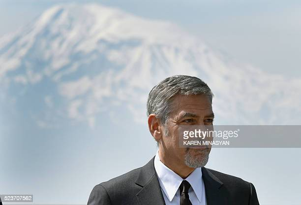 US actor George Clooney poses with Ararat mountain in background as he attends a ceremony at the Armenian Genocide Memorial in Yerevan on April 24...