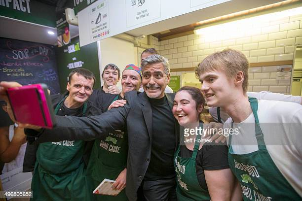 Actor George Clooney poses with former homeless staff members during a visit to Social Bite sandwich shop on November 12 2015 in Edinburgh Scotland