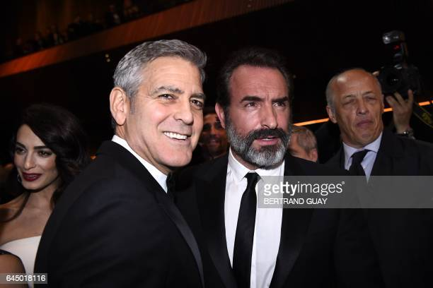 US actor George Clooney poses with French actor Jean Dujardin as they arrive for the 42nd edition of the Cesar Ceremony at the Salle Pleyel in Paris...