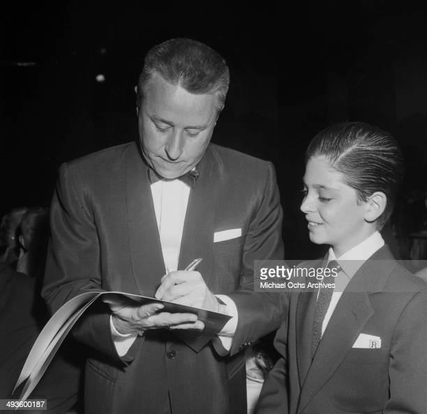 Actor George Gobel autographs a book for actor Tommy Rettig during the Emmy Awards in Los Angeles California
