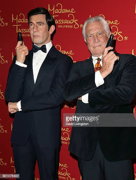 Actor George Lazenby poses with his wax figure at Madame Tussauds on December 15 2015 in Hollywood California