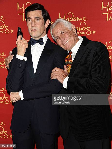 Actor George Lazenby poses with his wax figure at the unveiling of all six James Bond wax figures at Madame Tussauds on December 15 2015 in Hollywood...