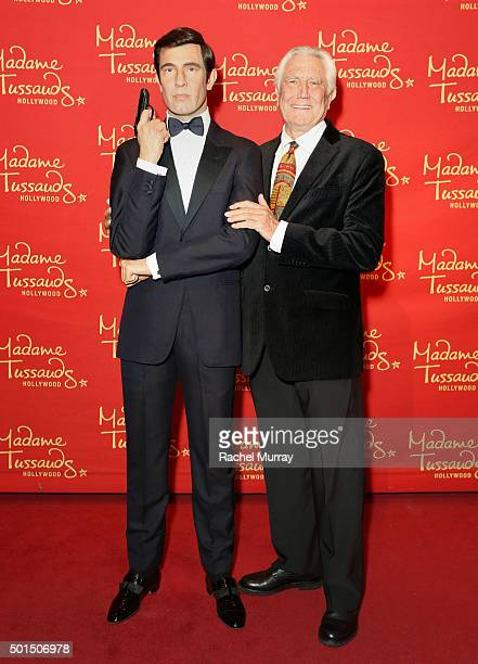 Actor George Lazenby poses with his wax figure during Madame Tussauds Hollywood reveal of all six James Bonds in wax with special guest George...