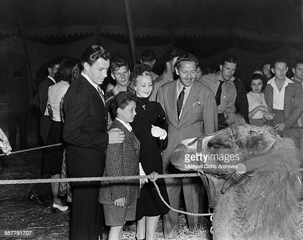 Actor George Murphy with his son and actress Ann Sothern and her husband actor Roger Pryor look at a camel as they attend the circus in Los Angeles...