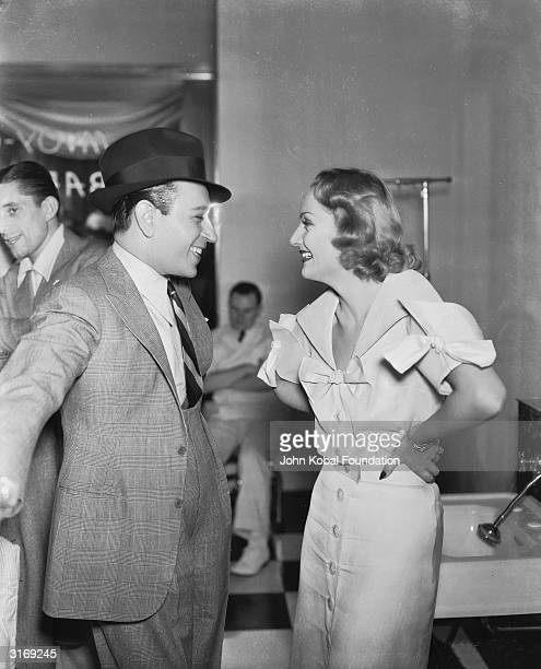 Actor George Raft visiting Carole Lombard on the set of 'hands Across The Table'