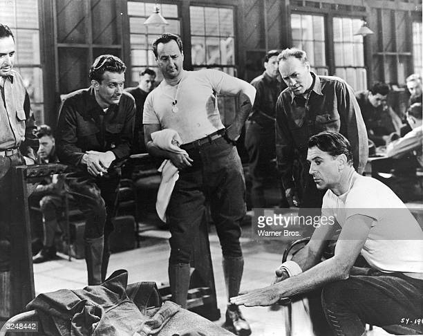 Actor George Tobias stands with others watching actor Gary Cooper in a still from the film 'Sergeant York' directed by Howard Hawks
