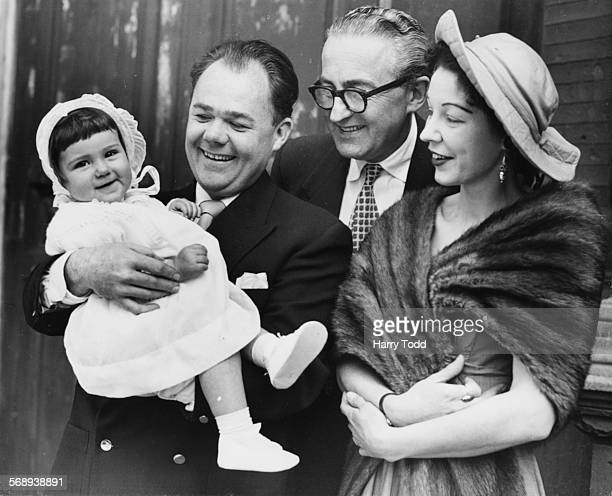 Actor Gerald Campion holding his god daughter Joanna with her parents Desmond and Barbara Davis after the baby's christening at the Church of the...