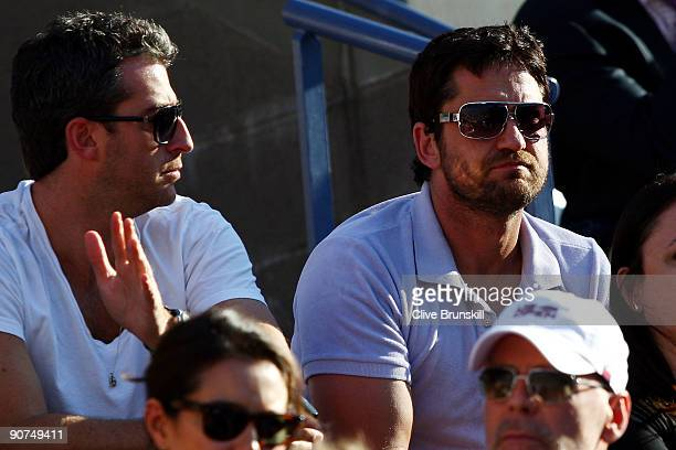 Actor Gerard Butler and Mark Birnbaum watches the match between Roger Federer of Switzerland and Juan Martin Del Potro of Argentina on day fifteen of...