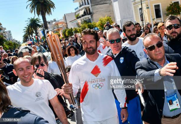 Actor Gerard Butler holds the Olympic flame during the Olympic flame relay in Sparta on March 13, 2020 ahead of the Tokyo 2020 Olympic Games.