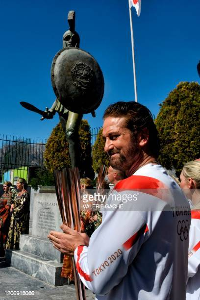 Actor Gerard Butler looks on as he stands under a statue of the ancient Spartan King Leonidas during the Olympic flame relay in Sparta on March 13,...