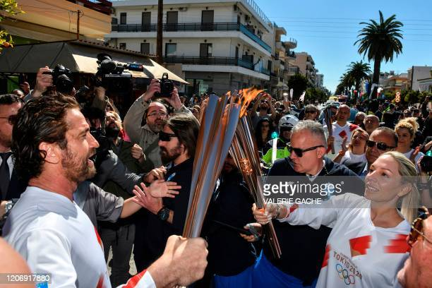 Actor Gerard Butler passes the Olympic flame during the Olympic flame relay in Sparta on March 13, 2020 ahead of the Tokyo 2020 Olympic Games.