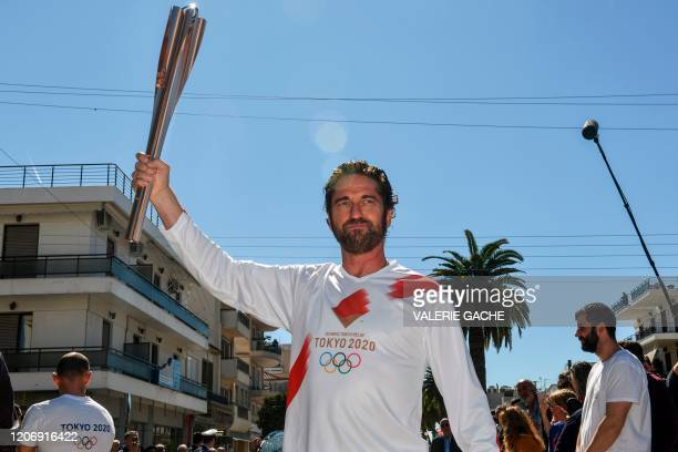 Actor Gerard Butler poses with the Olympic flame during the Olympic flame relay in Sparta on March 13, 2020 ahead of the Tokyo 2020 Olympic Games.